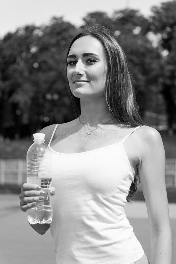 Água da bebida da mulher do frasco foto de stock