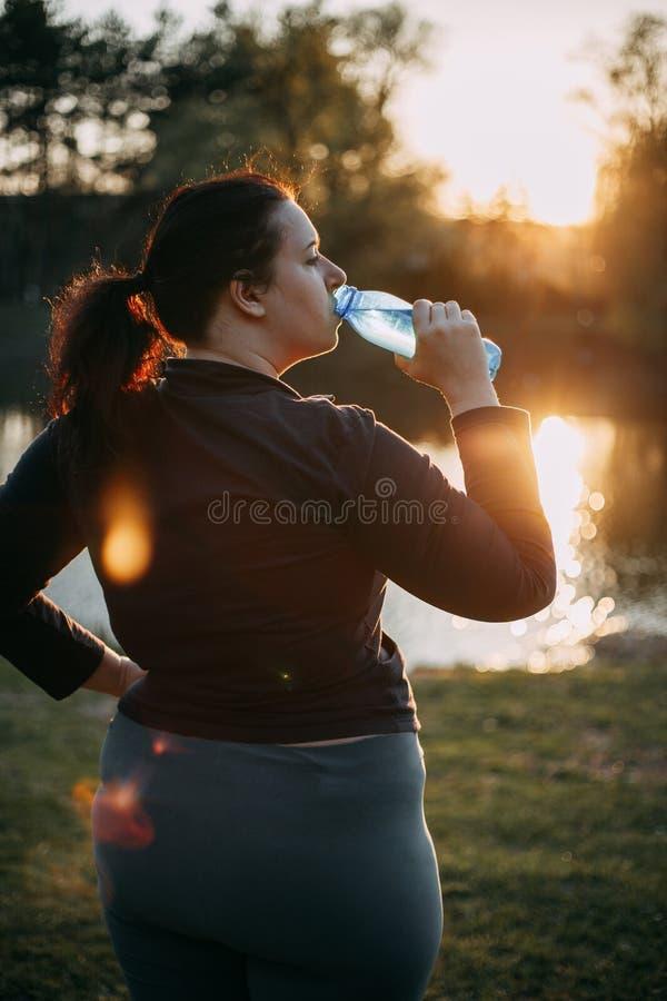 água da bebida da mulher do Mais-tamanho que anda fora foto de stock