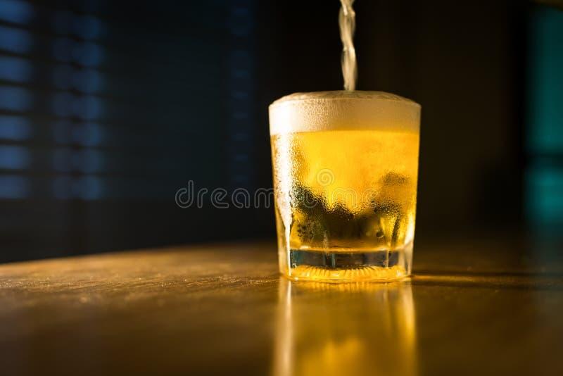 A água da cerveja nos vidros no restaurante do bar na noite pôs sobre a tabela fotos de stock royalty free