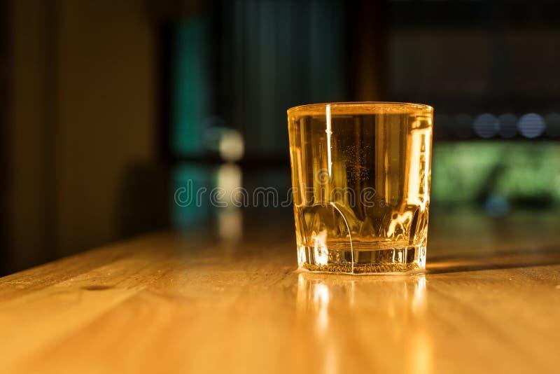 A água da cerveja nos vidros no restaurante do bar na noite pôs sobre a tabela foto de stock