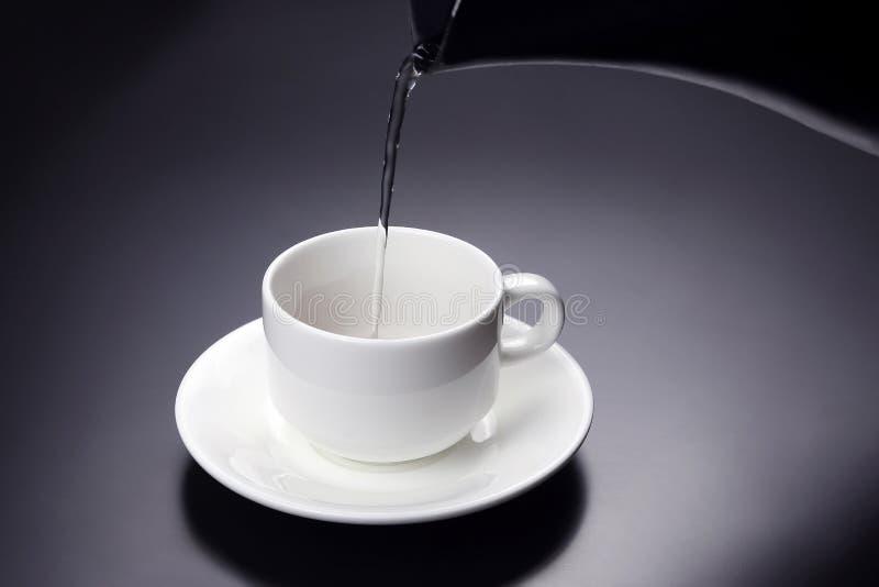 A água da chaleira é derramada em um copo para o café imagem de stock royalty free