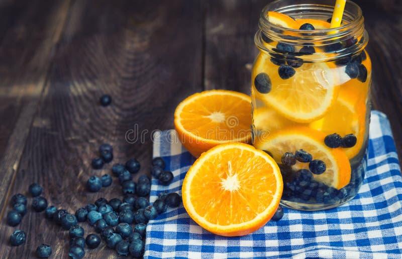 Água da desintoxicação com laranja e mirtilos no frasco fotos de stock royalty free