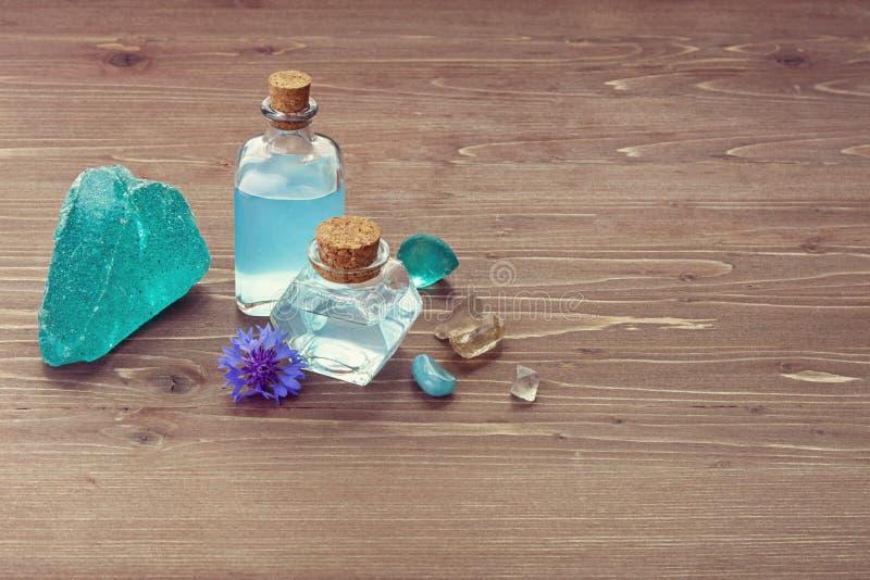 Água da flor da centáurea ou óleo essencial, hydrolate azul na garrafa de vidro e pedra mineral natural no fundo de madeira da ta fotos de stock