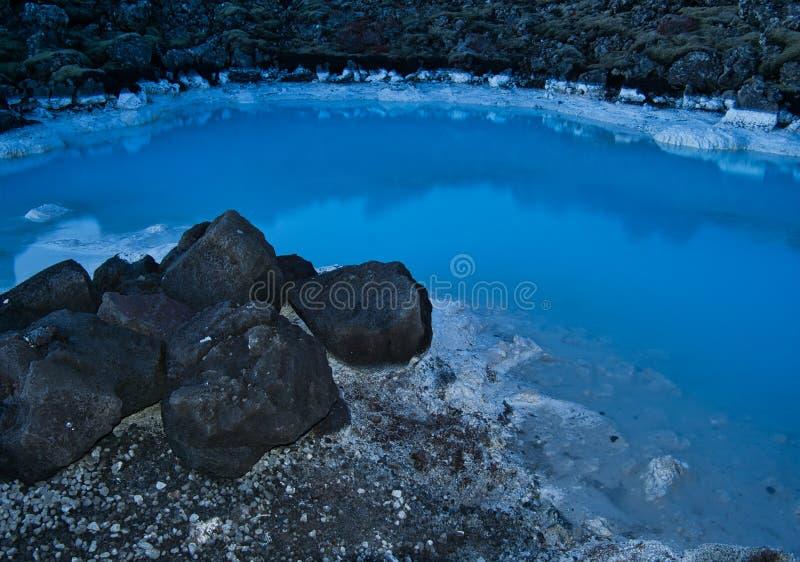 A água da lagoa azul cercada por rochas imagens de stock