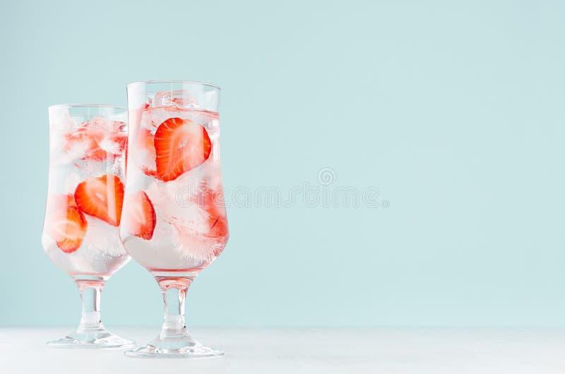 Água da morango com fatias vermelhas do fruto, cubos de gelo, água gasosa em dois vidros misted no interior moderno da cor da hor foto de stock royalty free