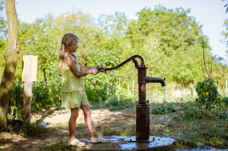 Água de bombeamento da criança pequena do poço de água fotografia de stock royalty free