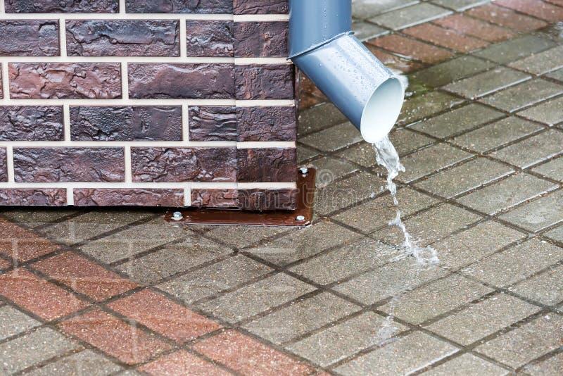 Água de chuva que flui de um downspout imagens de stock