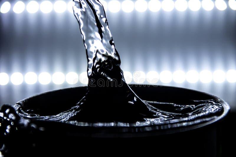 A água de derramamento causa dramaticamente a bolha ocorre com iluminação mais não ofuscante fotografia de stock royalty free