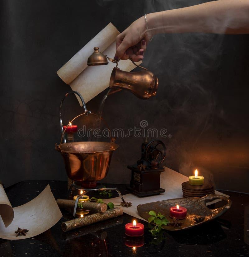 Água de derramamento da mão da mulher na chaleira do coper fotografia de stock royalty free
