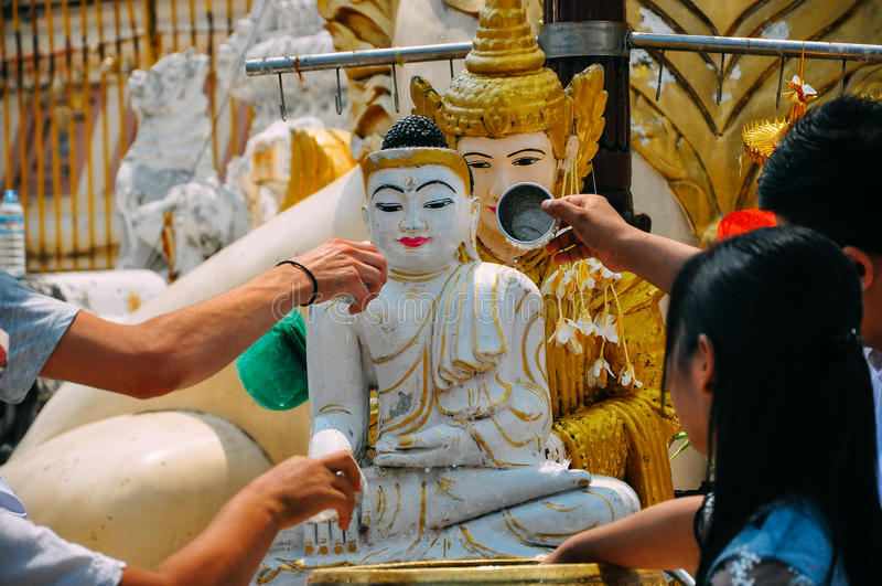 Água de derramamento dos povos na estátua da Buda no pagode de Shwedagon em Yangon fotos de stock
