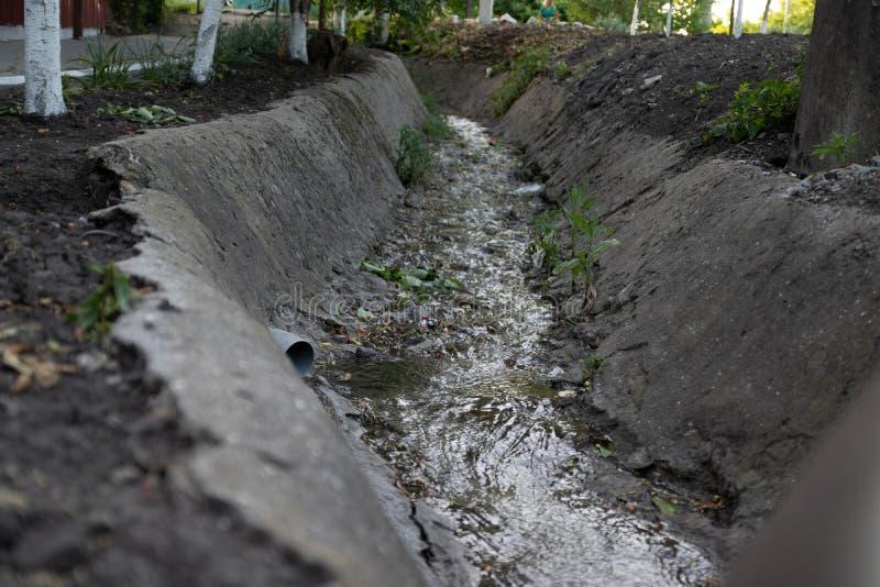 A água de esgoto do esgoto polui um lago Dreno de fluxo da poluição fotos de stock