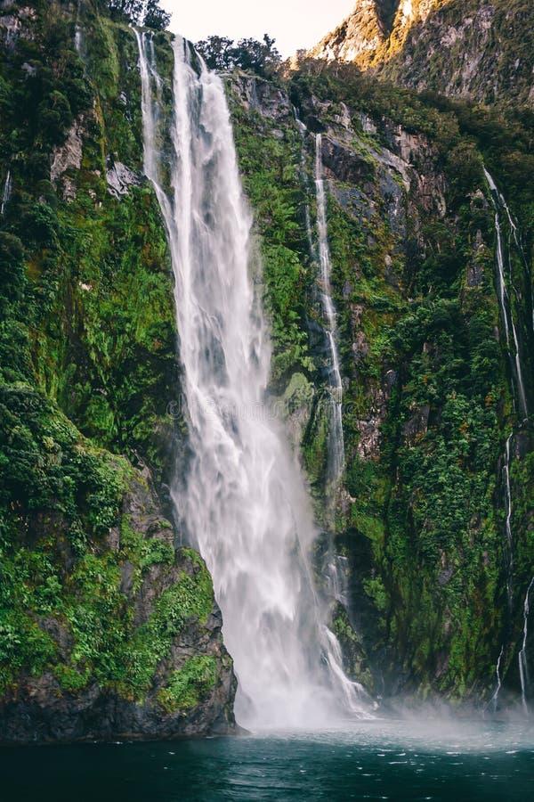 A água de fluxo cai no lago com musgo e as folhas verdes fotos de stock royalty free