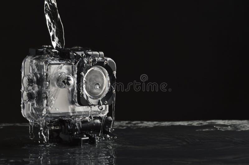 Água de fluxo na câmera impermeável da ação no fundo de pedra preto molhado imagens de stock royalty free
