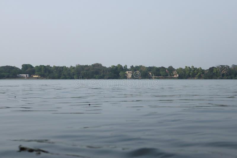 Água de fluxo no rio de Ganga na Índia e nas casas e templo no outro lado imagens de stock royalty free