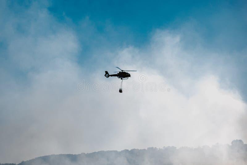 Água de lançamento do helicóptero durante um incêndio florestal foto de stock royalty free