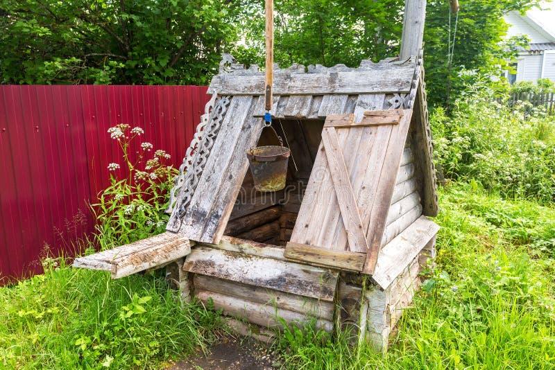 Água de madeira da vila velha bem no campo no verão imagem de stock
