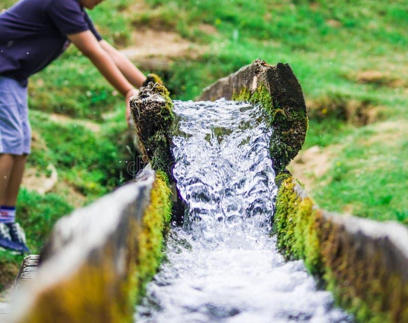 A água de mola clara desce para o vale com um menino novo foto de stock royalty free