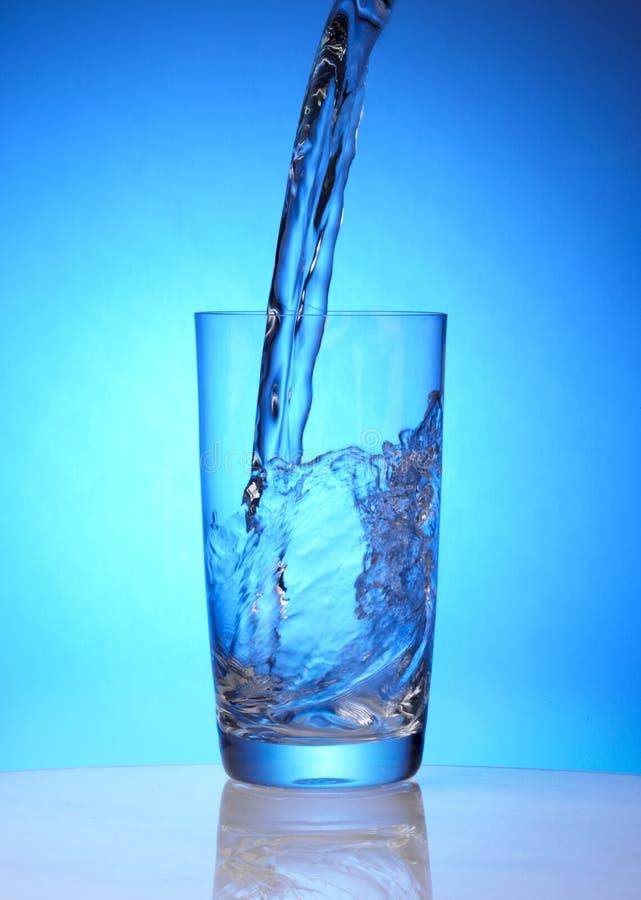A água de mola derrama no vidro imagens de stock royalty free