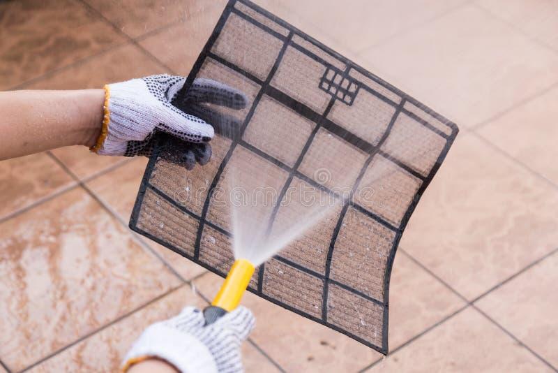 Água de pulverização da pessoa no filtro do condicionador de ar para limpar a poeira imagens de stock