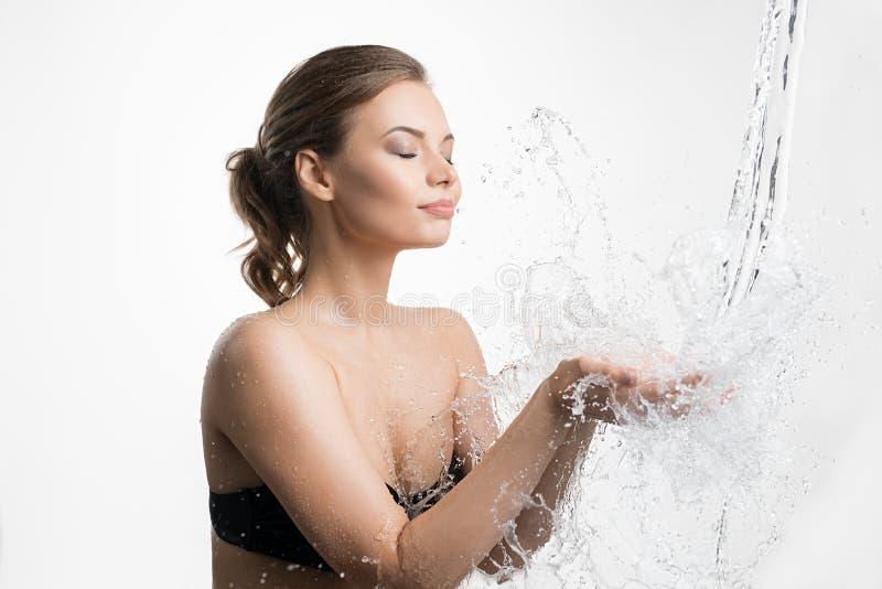 A água de travamento da jovem mulher espirra em suas mãos imagens de stock