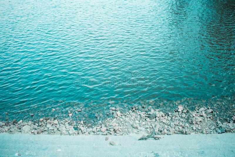a água de turquesa é uma terraplenagem da cidade com lajes fotos de stock royalty free