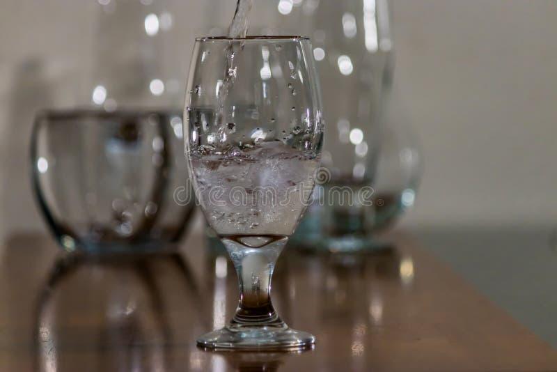 Água derramada sobre o gelo no vidro imagem de stock royalty free