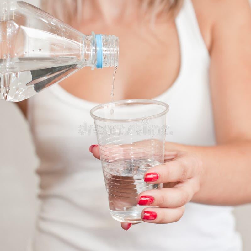 A água derramou de um frasco em um copo plástico imagens de stock
