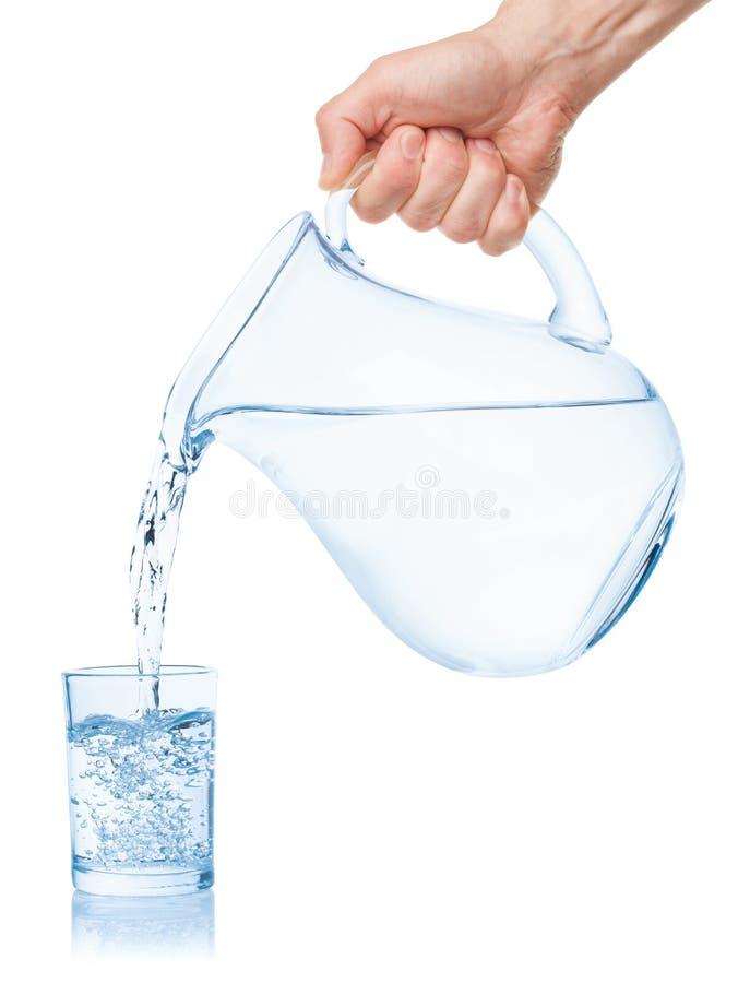 A água derramou do jarro em um vidro foto de stock royalty free