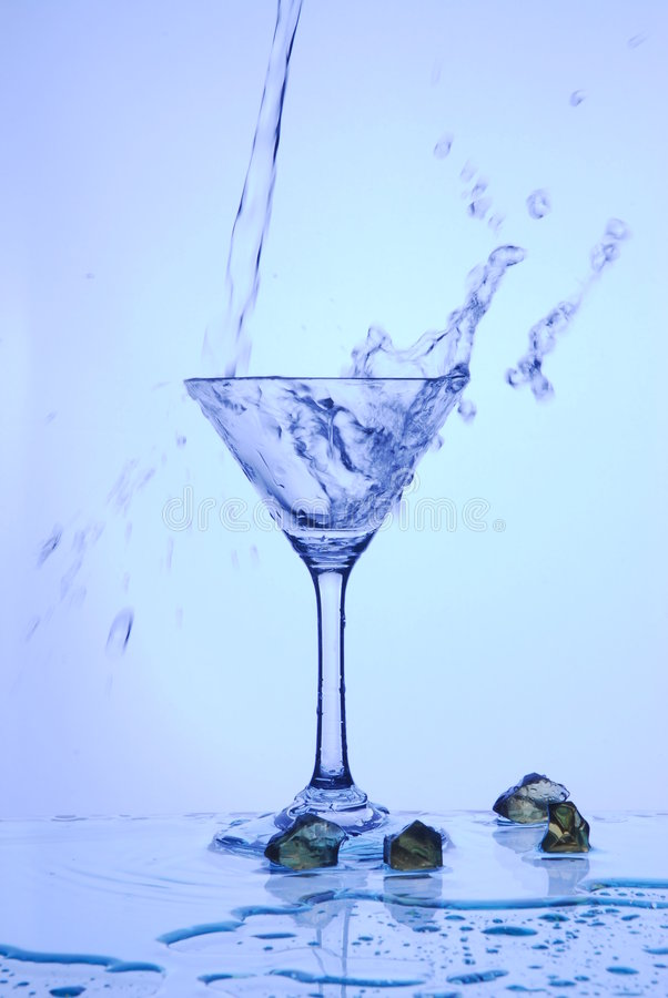 A água derramou no copo foto de stock