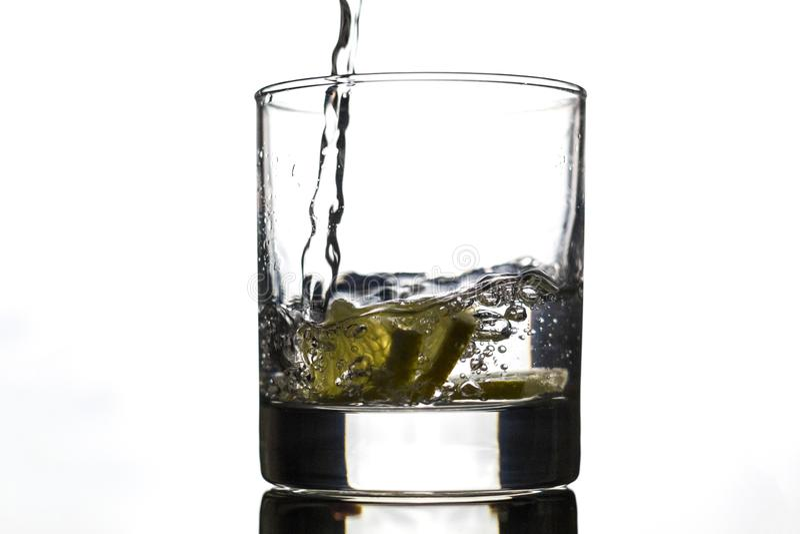 A água derramou no vidro com o limão - amarelo em um fundo branco imagem de stock