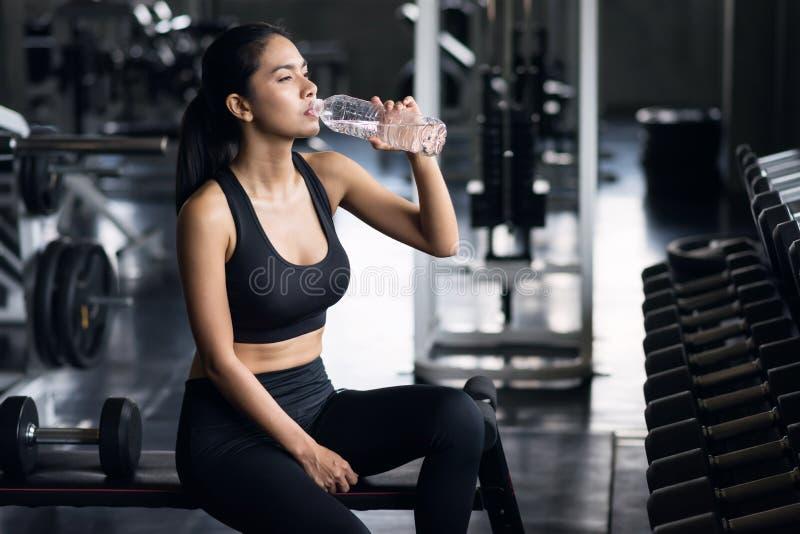 Água desportiva da bebida da menina após o exercício do peso imagem de stock