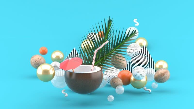 A água do coco e o coco estão entre as bolas coloridas no fundo azul imagem de stock royalty free