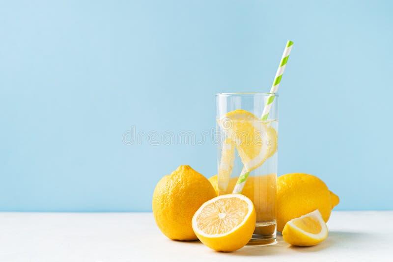 Água do limão da desintoxicação com metade do fruto dos limões e completo no fundo azul fotos de stock royalty free