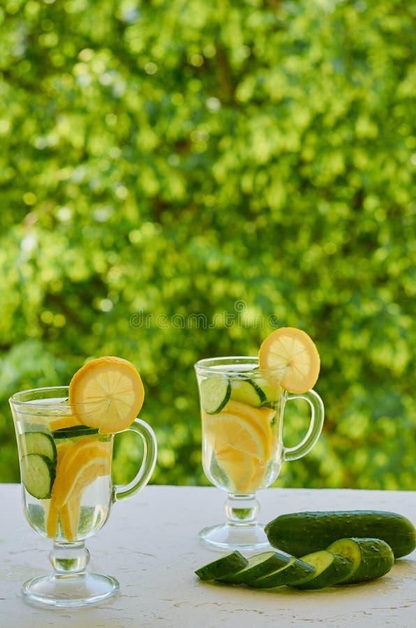 Água do limão em dois vidros com fatias do gelo e do pepino no fundo borrado da natureza Cocktail do frio do verão Bebidas saudáv imagens de stock royalty free
