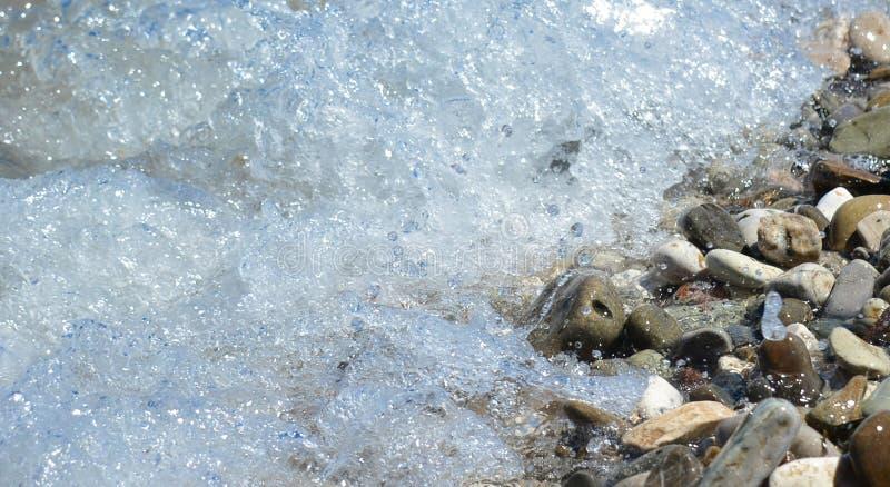 A água do mar clara espirra nas pedras imagens de stock
