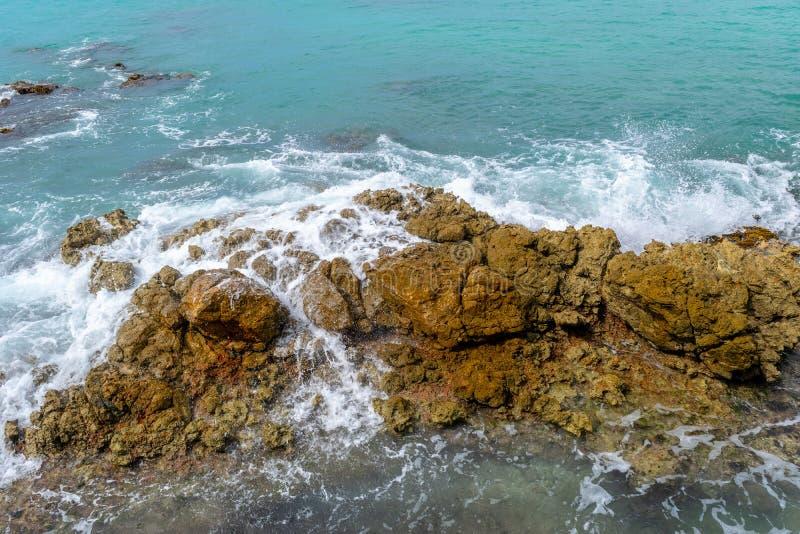 Água do mar de turquesa que deixa de funcionar em rochas no dia de verão ensolarado imagem de stock