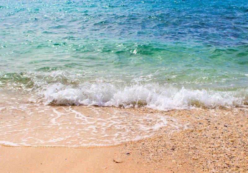 Água do mar de turquesa sobre a praia branca da areia A onda limpa e relaxando do mar espirra sobre o litoral fotos de stock royalty free