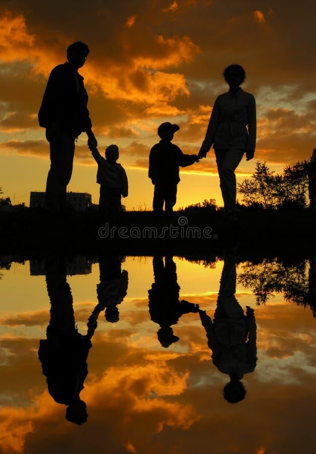 Água do por do sol do agregado familiar com quatro membros imagens de stock royalty free