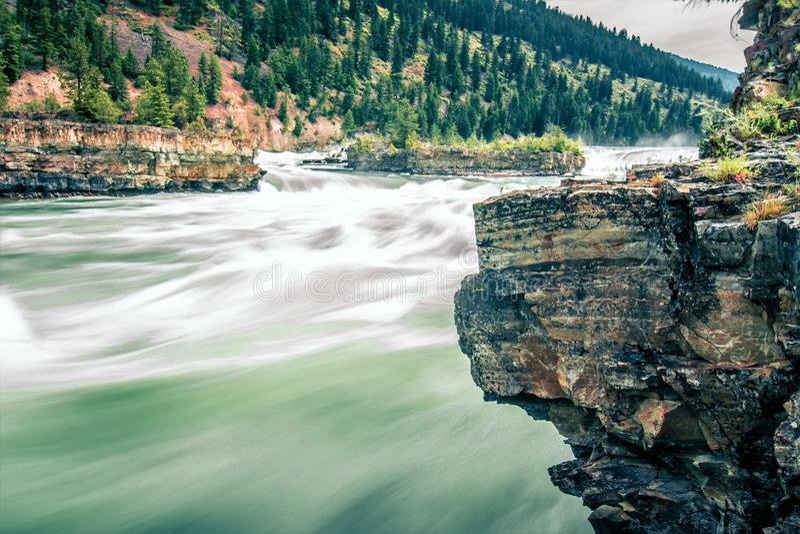 A água do rio de Kootenai cai em montanhas de montana imagem de stock