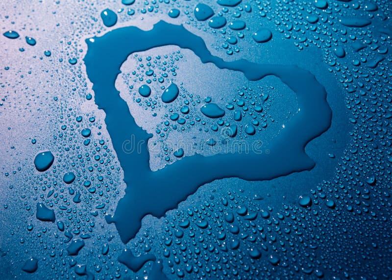 água e gotas do coração no fundo azul fotografia de stock royalty free