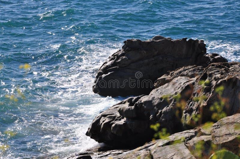 Água, espuma do mar e rochas fotografia de stock royalty free