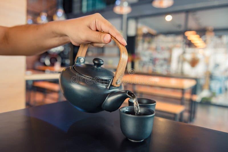 Água a ferver de derramamento da chaleira em um copo durante o tempo do café na cafetaria foto de stock royalty free
