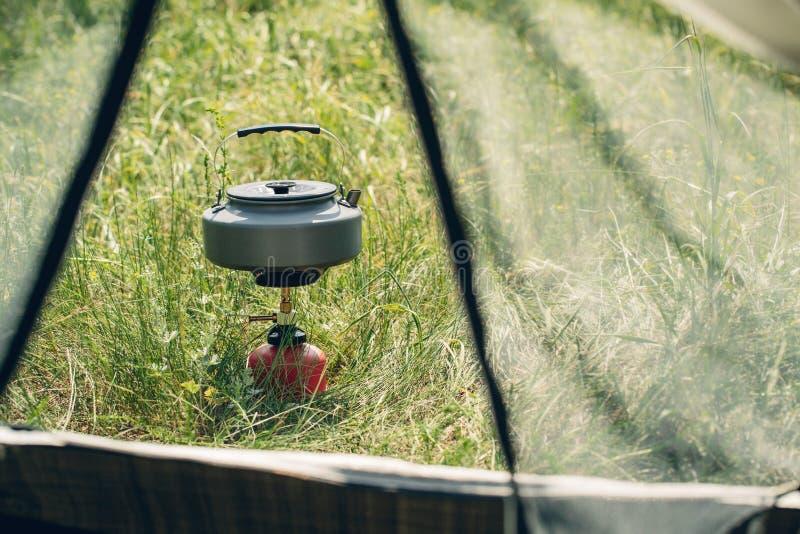 Água a ferver na chaleira no fogão de acampamento portátil imagem de stock