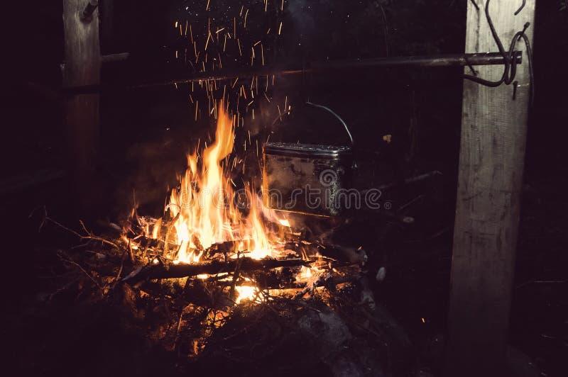 Água a ferver no jogador na fogueira imagem de stock royalty free