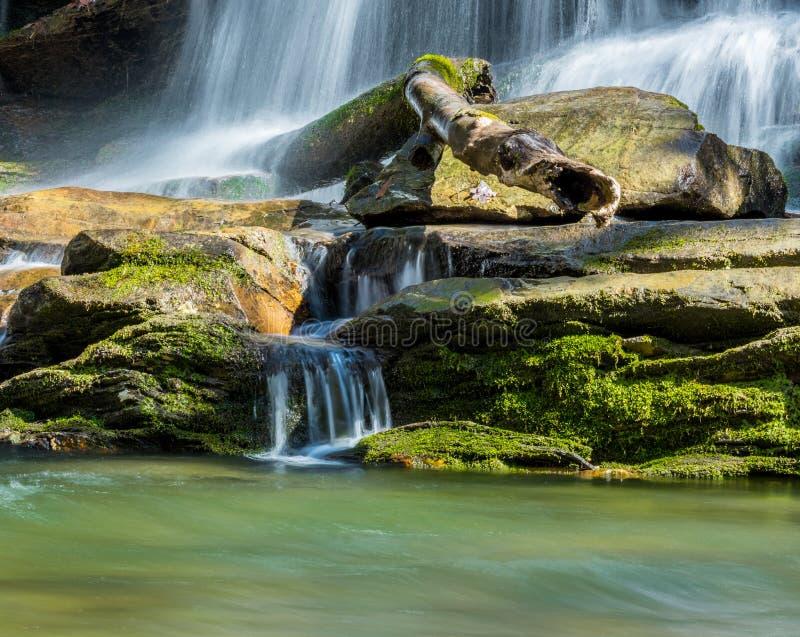 A água flui abaixo de Moss Covered Rocks fotografia de stock royalty free