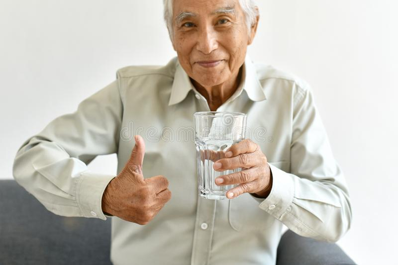 A água fresca bebendo é bom hábito saudável para o ancião, polegar asiático de sorriso idoso da mostra do homem até o vidro da ág imagens de stock royalty free