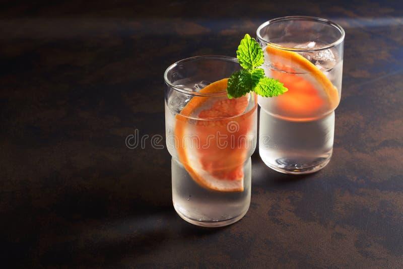 Água fria de refrescamento em um vidro com fatias de toranja e de hortelã Copie o espaço Desintoxicação da bebida do verão fotos de stock royalty free