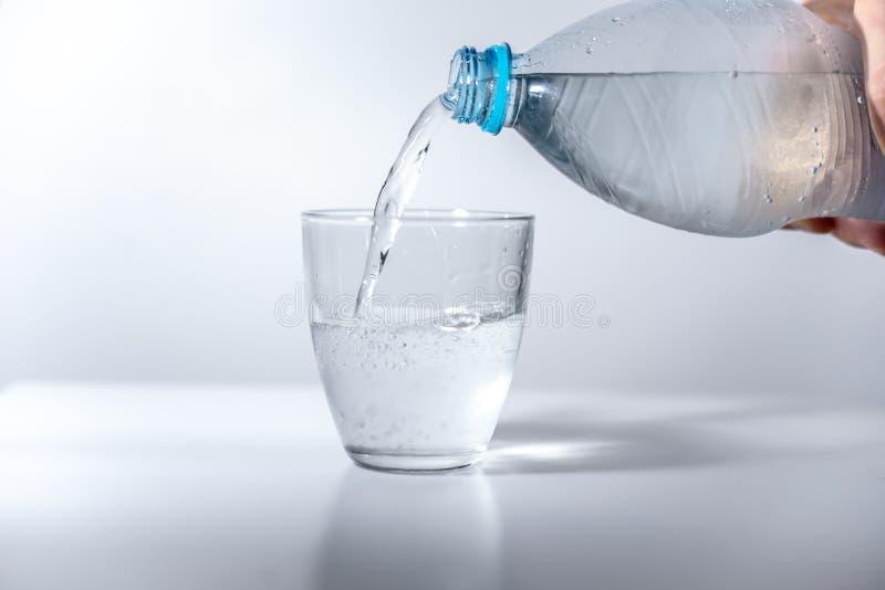 Água gasosa de derramamento da mão da garrafa plástica ao vidro enchido com água mineral fria na superfície brilhante, vazia Refl foto de stock