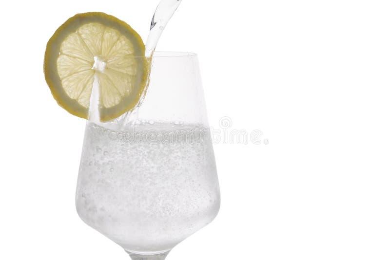 Água gasosa que está sendo derramada em um vidro com uma fatia de limão fotografia de stock