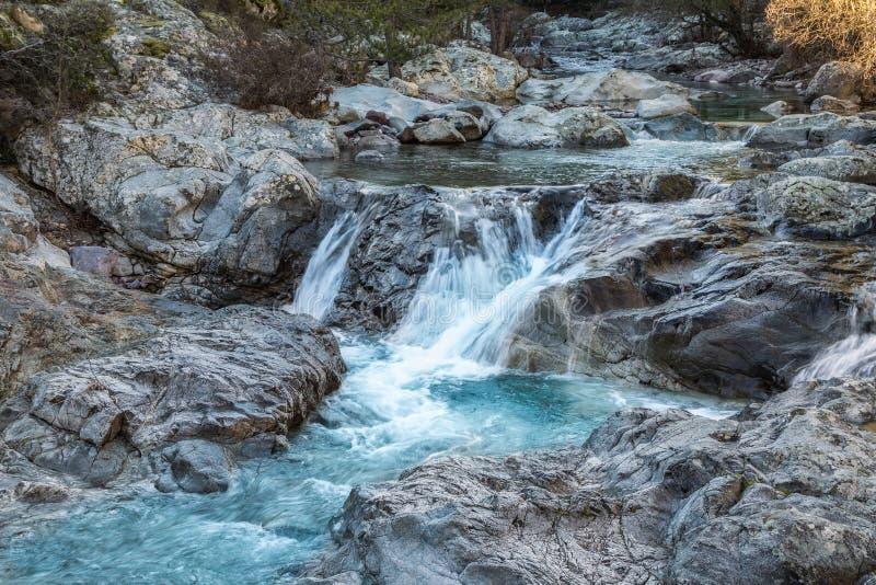 Água gelada que flui sobre rochas em Córsega imagens de stock